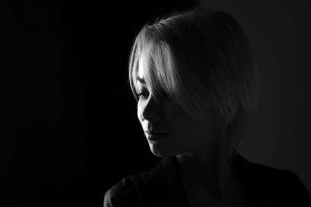 Photo pour Portrait of a young sad woman close-up looking away, dark black and white photo - image libre de droit