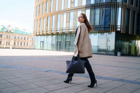 Photo for A business woman in a coat and suit, holding a bag in her hand, walks near the business center during the day. Conceptual horizontal photo - Royalty Free Image
