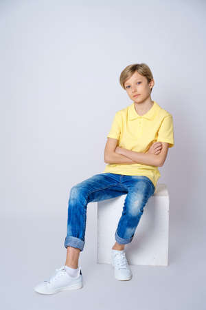 Foto de A cute guy in a yellow t shirt and blue jeans on a white background is sitting on a cube and posing - Imagen libre de derechos