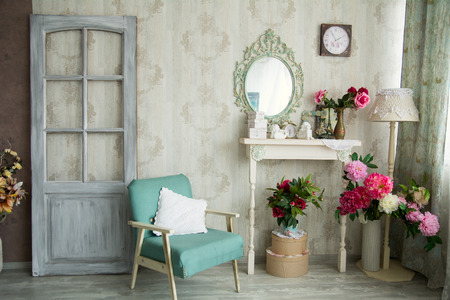 Vintage country house interior with mirror and a table with a vase and flovers. Interior design with a door and an old chair.