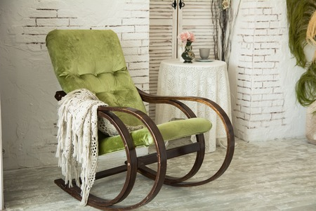 Green rocking chair on a background of a brick wall in the interior of the house. Retro background for the elderly