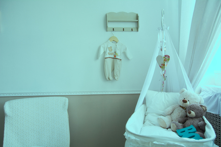 Interior of a nursery with a crib for a baby. Background with baby furniture and teddy bears in the crib
