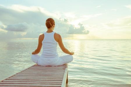 Photo pour Caucasian woman practicing yoga at seashore - image libre de droit