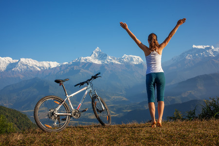 Photo pour woman practicing yoga, relaxing after riding bikes high in mountain - image libre de droit