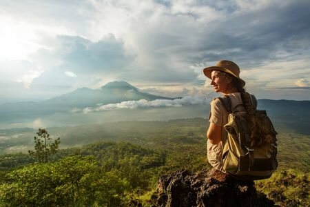 Photo for Woman enjoying sunrise from a top of mountain Batur, Bali, Indonesia. - Royalty Free Image