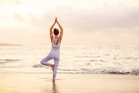 Photo for Woman practices yoga at seashore - Royalty Free Image
