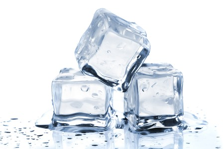 Three melting ice cubes on glass table. On white background