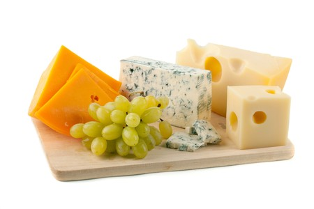 Cheese and grapes. Isolated on white