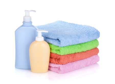 Cosmetics bottles and towels. Isolated on white background