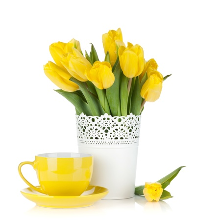 Yellow tulips and tea cup. Isolated on white background