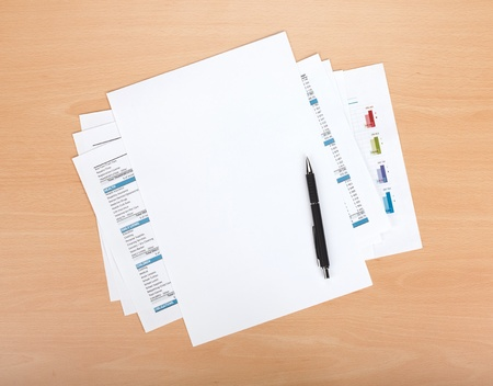 Blank paper with pen over financial documents