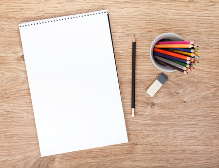 Blank paper and colorful pencils on the wooden table. View from above