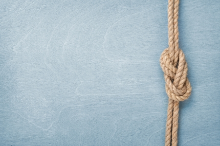 Ship rope knot on blue wooden texture background