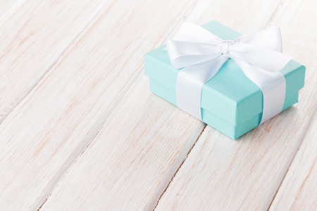 Gift box with bow over white wooden table with copy space