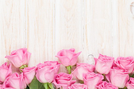 Valentines day background with pink roses over wooden table. Top view with copy spaceの写真素材