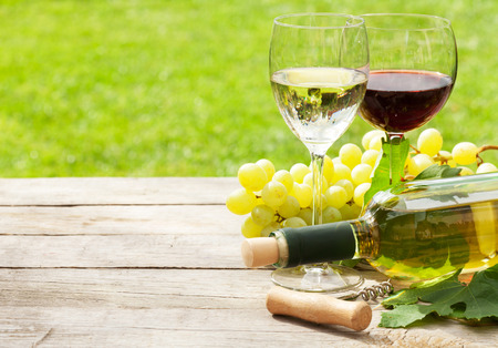 White and red wine glasses, wine bottle and white grape on wood table with copy space