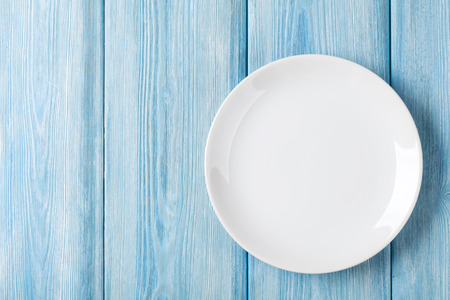 Empty plate on blue wooden background. Top view with copy space