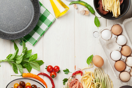 Pasta cooking ingredients and utensils on wooden table. Top view with copy space