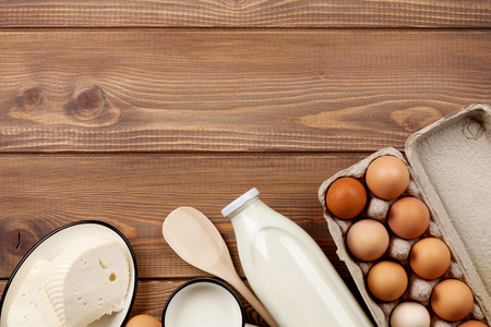 Dairy products on wooden table. Milk, cheese and eggs. Top view with copy space