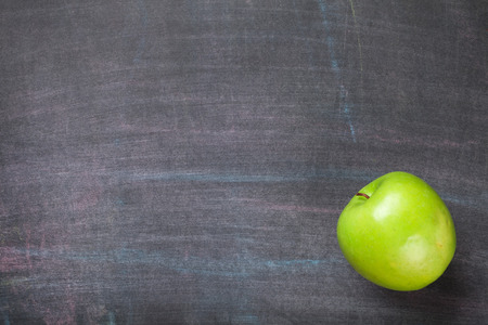 Green apple on blackboard or chalkboard background. Top view with copy space
