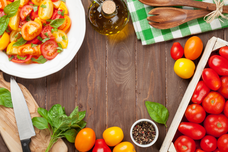 Fresh colorful tomatoes and basil salad on wooden table. Top view with copy space