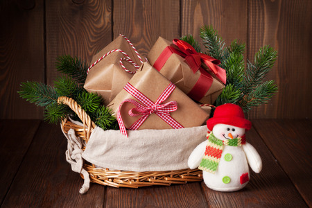 Christmas gift boxes and fir tree in basket with snowman toy