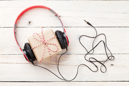 Gift box with headphones on wooden table. Top viw