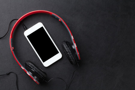 Headphones and smartphone on black leather desk table. Top view with copy space