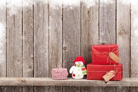 Christmas gift boxes and snowman toy in front of wooden wall. View with copy space