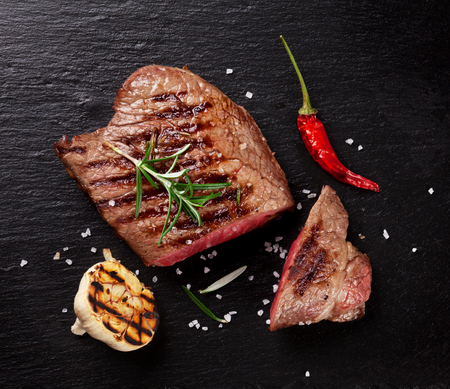 Grilled beef steak with rosemary, salt and pepper on black stone plate. Top view