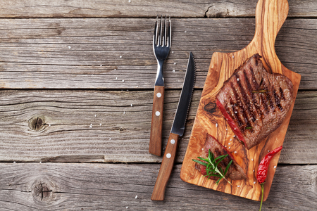 Grilled beef steak with rosemary, salt and pepper on wooden table. Top view with copy space
