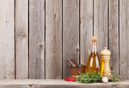 Photo for Kitchen utensils, herbs and spices on shelf against rustic wooden wall - Royalty Free Image