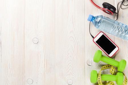 Photo pour Dumbbells, water bottle, smartphone, headphones and tape measure. Top view with copy space - image libre de droit