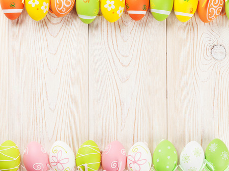 Easter background with colorful eggs over wooden table. Top view with copy space