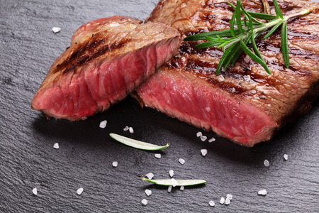 Photo pour Grilled beef steak with rosemary, salt and pepper on black stone plate - image libre de droit
