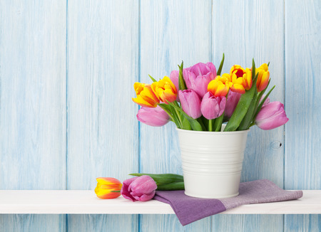 Photo pour Fresh colorful tulip flowers bouquet on shelf in front of wooden wall. View with copy space - image libre de droit