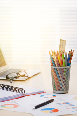 Photo pour Office workplace with with laptop, reports and pencils on wooden desk table in front of window with blinds. Sunset light - image libre de droit