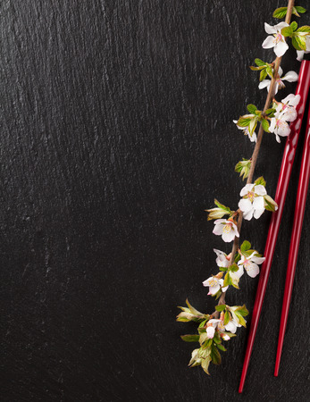 Photo pour Japanese sushi chopsticks and sakura blossom on black stone background. Top view with copy space - image libre de droit