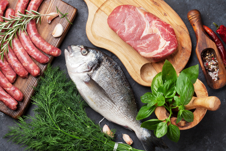 Photo pour Sausages, fish, meat and ingredients cooking. Top view on stone table - image libre de droit