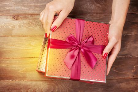 Foto de Female hands opening christmas or valentines day gift box above wooden table. Top view - Imagen libre de derechos