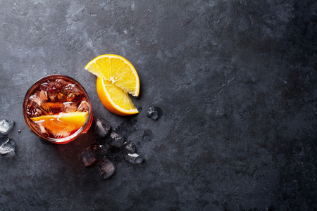 Photo pour Negroni cocktail on dark stone table. Top view with space for your text - image libre de droit