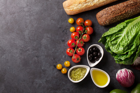 Photo for Cooking food ingredients. Lettuce salad, avocado, olives, bread and tomato cherry over stone background. Top view with copy space - Royalty Free Image
