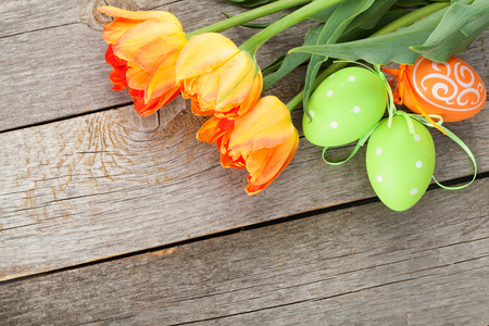 Easter eggs and tulip flowers on wooden table. Top view with copy space