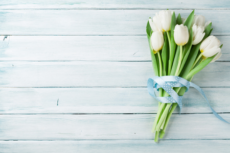 White tulips bouquet on wooden background. Top view with space for your text