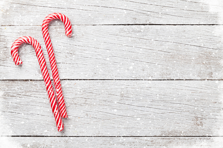 Photo pour Christmas candy canes on wooden table. Top view with space for your greetings - image libre de droit