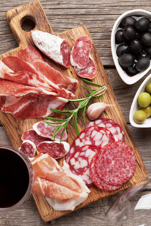 Salami, sliced ham, sausage, prosciutto, bacon, toasts, olives. Meat antipasto platter and red wine on wooden table. Top view
