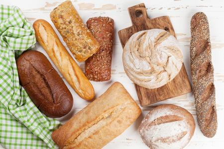 Photo pour Various crusty bread and buns on white wooden table. Top view - image libre de droit