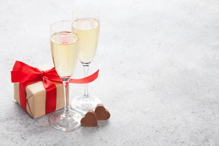 Photo for Valentines day greeting card with champagne, gift box and chocolate hearts on stone background. With space for your greetings - Royalty Free Image