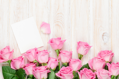 Photo pour Pink roses over wooden table. Top view with greeting card for your text - image libre de droit