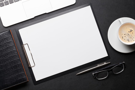 Photo pour Office workplace table with blank paper page, coffee cup, supplies and laptop. Flat lay. Top view with space for your goals - image libre de droit